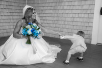 Bridal trends - Bride with only flowers in color playing tug a war with young boy.