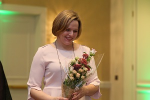 Heather, manager at Lahey Clinic stands holding flowers she has just been given for presenting the awards banquet for the graduating doctors of Lahey Clinic.