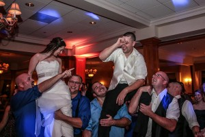 Bride and Groom being held up high by their friends