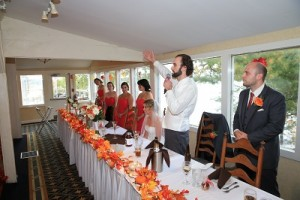 Groom holds microphone as he addresses his guests from the head table on his wedding day.
