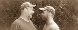 Wesley and Thomas were married May 11, 2015, Billerica, MA. They are facing each other in front of shrubs.