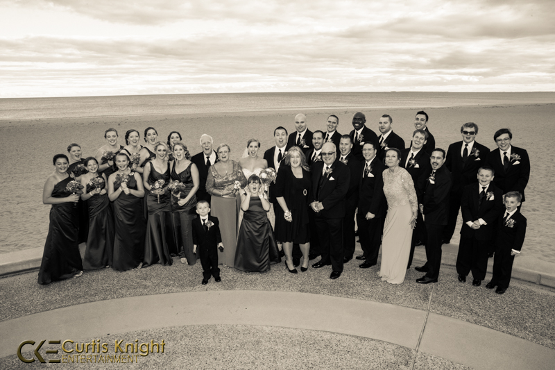 The bride, groom, bridesmaids, and more gather to pose by the beach after a magnificent wedding!