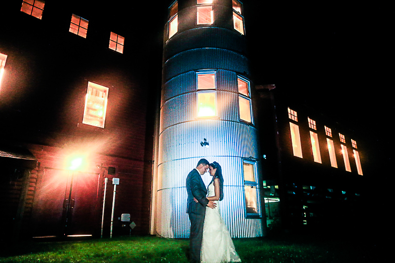 Bride & groom in wedding gown & tux facing each other, embracing, standing beside barn silo in darkness, with camera flash behind them lighting up the barn & silo