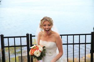 This photo shows a Bride as she sees her groom for the first time as he gets his first look at her.