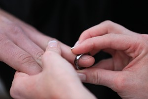 A close up photo of the ring exchange, showing hands and rings only during a wedding Ceremony with Justice of the Peace Curtis Knight.