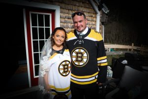 Smiling bride and groom on their wedding day wearing Boston Bruins hockey team shirts as a tribute to their favorite team.