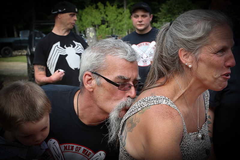 Celebration of life for a fallen soldier. In this photo, father of father of fallen soldier is kissing mother of fallen soldier