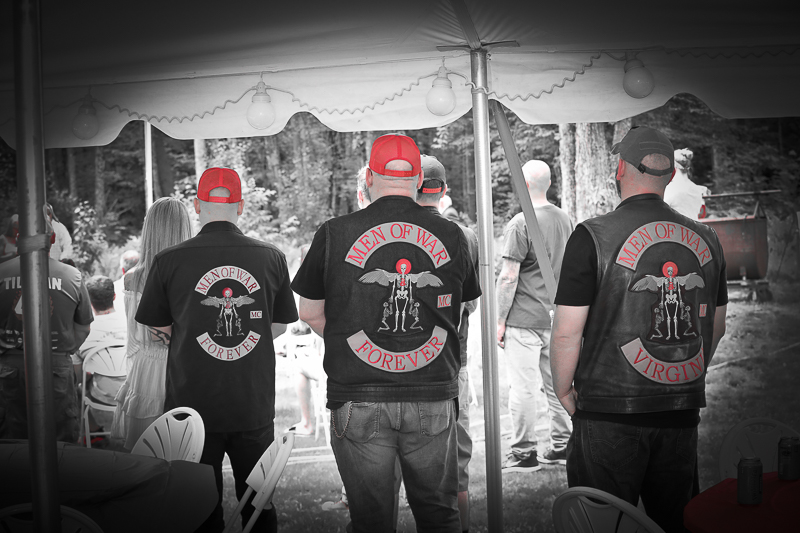 Celebration of life for a fallen soldier.Members of fallen soldiers motor cycle club Men of War stand with heads bowed during tribute.